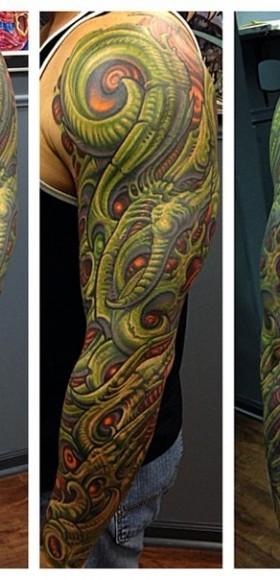 Цветная тату на руке парня в стиле биомеханика-органика