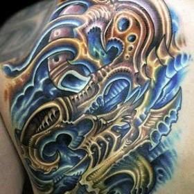 Цветная татуировка на лопатке парня в стиле биомеханика