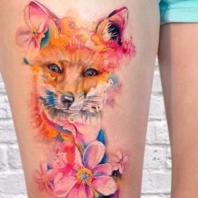 Фото красиового тату лисы в стиле акварель на бедре девушки