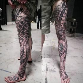 Фото крутой татуировки в стиле органика на ноге парня