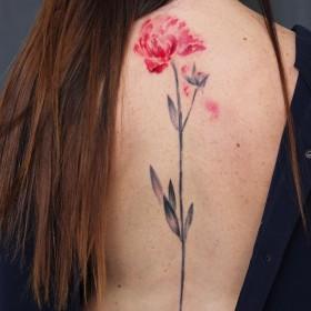 Фото тату цветка в стиле акварель на позвоночнике девушки
