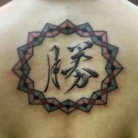 Фото тату иероглифа и мандалы на спине девушки