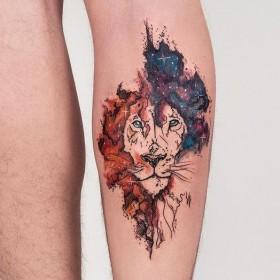 Фото тату льва в стиле акварель на голени парня