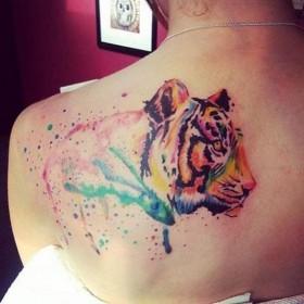 Фото тату тигра в стиле акварель на лопатке девушки