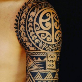 Фото тату в стиле полинезия на рукаве парня
