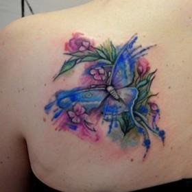 Фото татуировки бабочки в стиле акварель на лопатке девушки