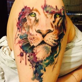 Фото татуировки льва в стиле акварель на плече девушки