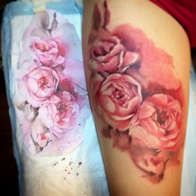 Фото татуировки пионов в стиле акварель на бедре девушки