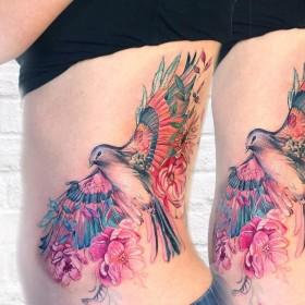 Фото татуировки птицы с цветами в стиле акварель на боку девушки