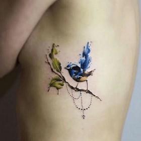 Фото татуировки птицы в стиле акварель на ребрах девушки