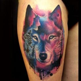 Фото татуировки волка в стиле акварель на бедре девушки
