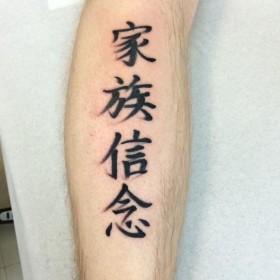 Фото татушки иероглифов на голени парня