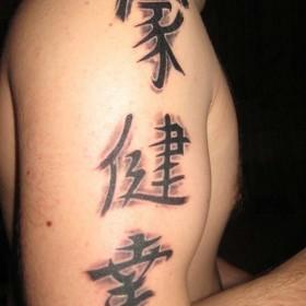 Фото татушки иероглифов на плече парня