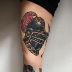 Изображение шлема рыцаря на бицепсе мужчины