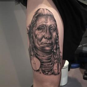 Крутая татуировка индейца на бедре девушки