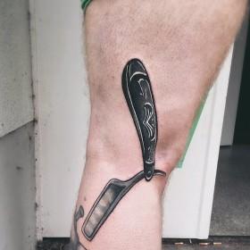 Крутое тату лезвия на ноге парня