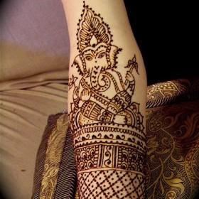 Рисунок черной хной на руке девушки - ганеша