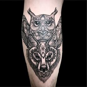 Рисунок тотема совы и волка на голени мужчины