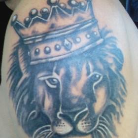 Тату корона на голове льва на плече у мужчины