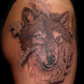 Тату на бедрах девушки - волк с листьями