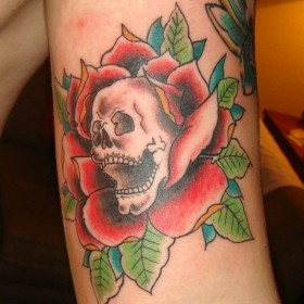 Тату на бицепсе парня - роза и череп