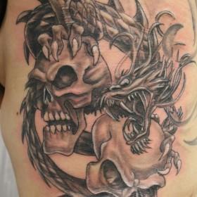 Тату на боку парня - дракон и черепа