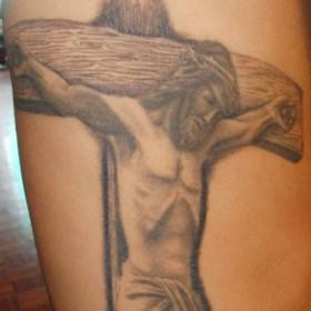 Тату на боку у парня - крест и распятый Иисус