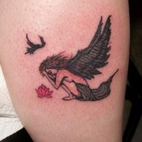 Тату на голени девушки - ангел, лотос и птица