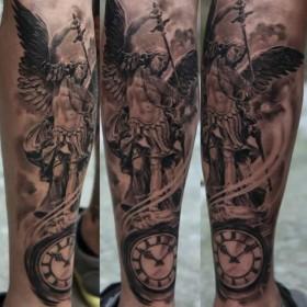 Тату на голени у девушки - ангел с мечом и часы