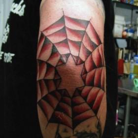 Тату на локте у парня в виде паутины и шестиконечной звезды