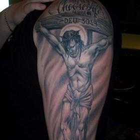 Тату на плече девушки - крест и распятый на нем Иисус