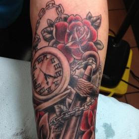 Тату на руке девушки - карманные часы, розы и якорь