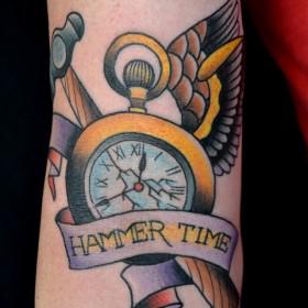 Тату на руке девушки - молот, часы с крыльями
