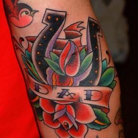 Тату на руке девушки - подкова, роза и надпись