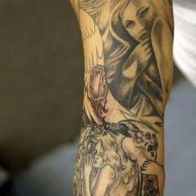 Тату на руке парня - ангел и демоны