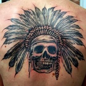 Тату на спине девушки - череп индейца