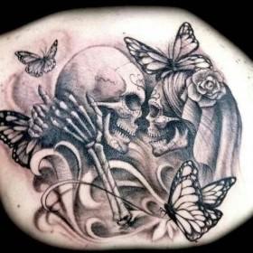 Тату на спине девушки - черепа и розы