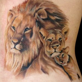 Тату на спине девушки - лев, львица и львенок