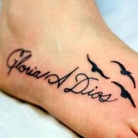 Тату на ступне у девушки - надпись на испанском и маленькие птички