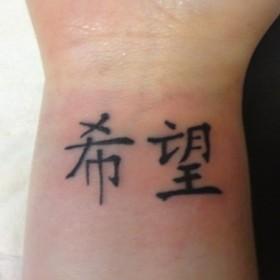 Тату на запястье девушки - китайские иероглифы