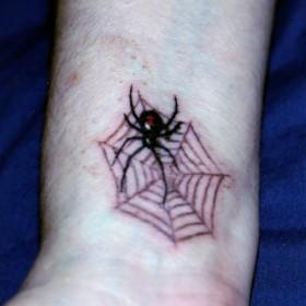 Тату на запястье парня - паутина и паук