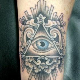 Тату на запястье парня - пирамида с глазом
