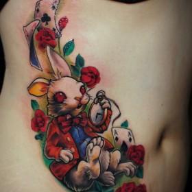 Тату на животе девушки - заяц, карты, часы и розы