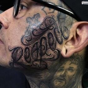 Тату - надпись в стиле чикано на лице парня