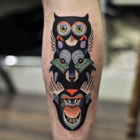 Тату тотема совы волка и обезьяны на голени парня