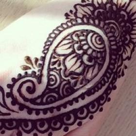 Роспись черной хной на руке девушки - огурцы