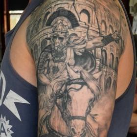 Татуха гладиатора на коне на плече мужчины