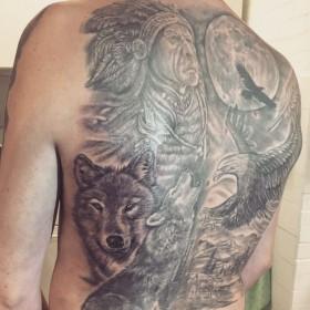 Татуха индейца с волками и орлом на спине мужчины