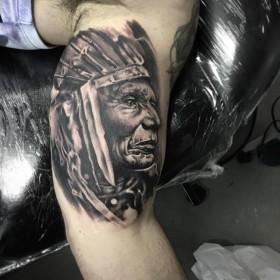 Татуировка индейца на бицепсе мужчины