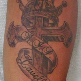 Татуировка корона, крест и лента с надписью на предплечье у мужчины